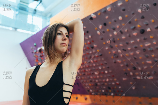 Young adult woman posing in a climbing wall gym looking camera - well being, healthy lifestyle, sportive concept