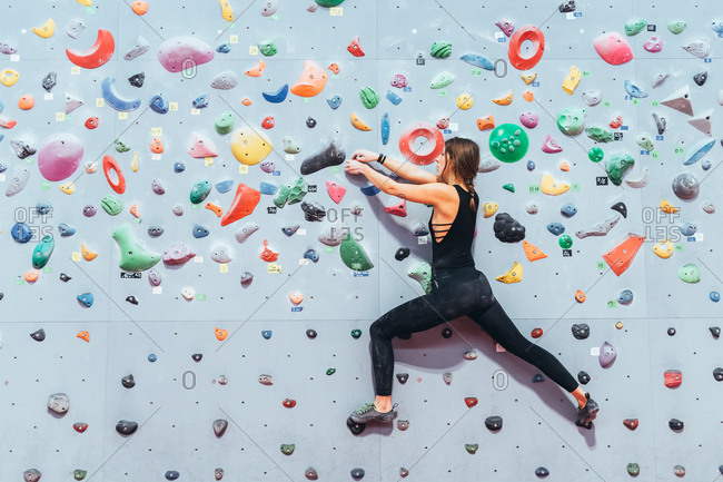 Young adult women posing in a climbing wall gym looking camera - well being, healthy lifestyle, sportive concept