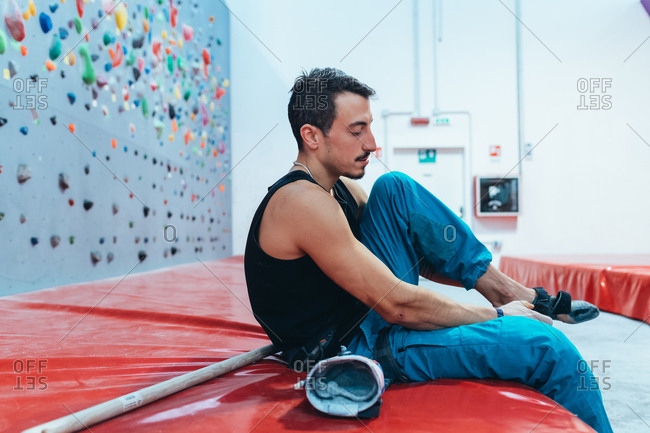 Young man preparing the wall for climbing in the gym - preparation, concentration, sportive concept