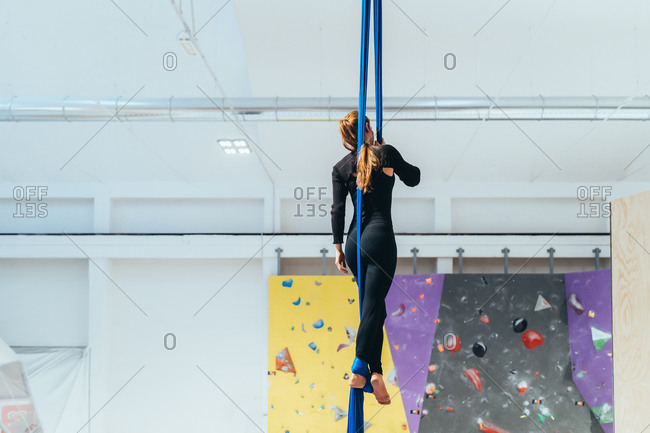 Young woman climbing rock wall indoor - sportive, athletic, balance concept