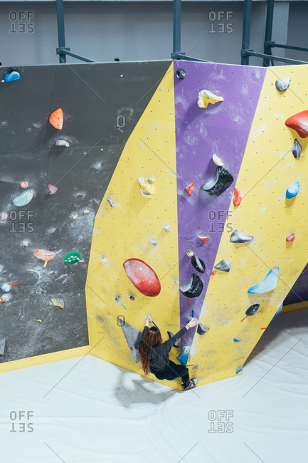 Young adult man posing in a climbing wall gym looking camera - well being, healthy lifestyle, sportive concept