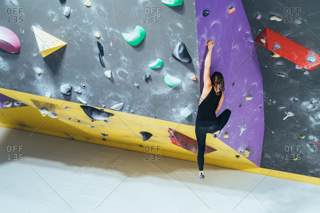 Unrecognizable young woman preparing himself in a climbing gym - preparation, concentration, sportive concept