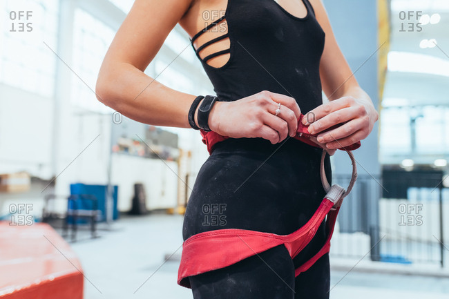 Young woman preparing himself in a climbing gym - preparation, concentration, sportive concept