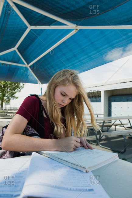 Blond teen girl with backpack studying at empty lunch tables with books and apple at middle school