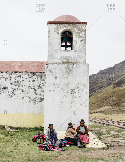 Lake Titicaca, Peru - November 22, 2017: Peruvian family sitting outside of church