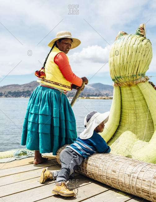 Lake Titicaca, Peru - November 23, 2017: Woman rowing boat while child looks into the distance