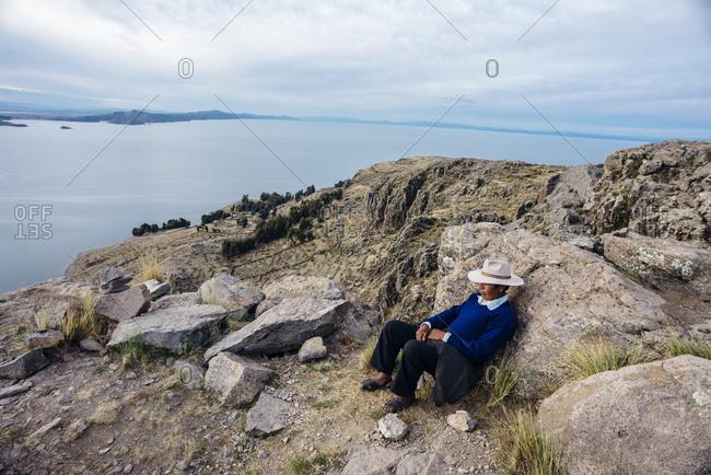 Lake Titicaca, Peru - November 23, 2017: Peruvian man sitting on rocky mountainside looking at lake