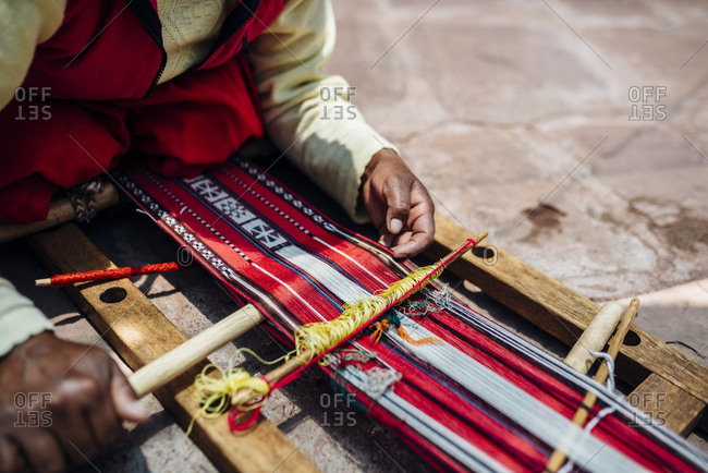 Person weaving traditional textiles, Peru