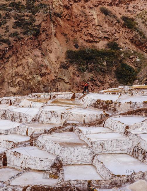 Man walking at the Inca salt ponds, Sacred Valley in Peru