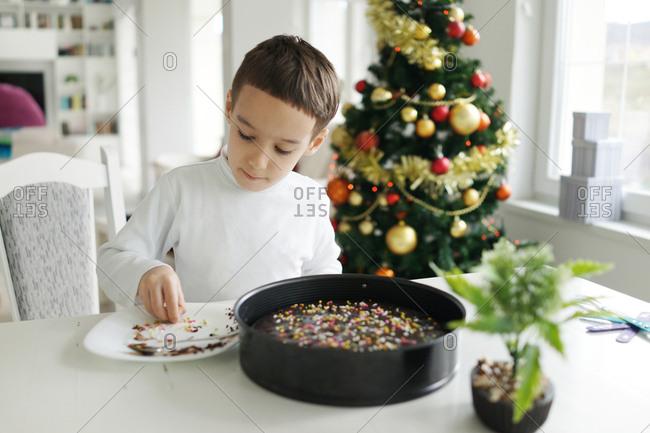 A little boy is making a cake