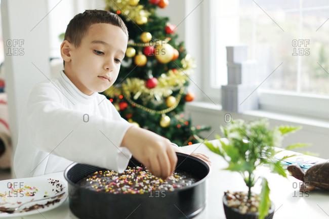 A little boy decorating a cake