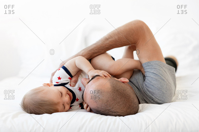 Father and happy baby playing on bed