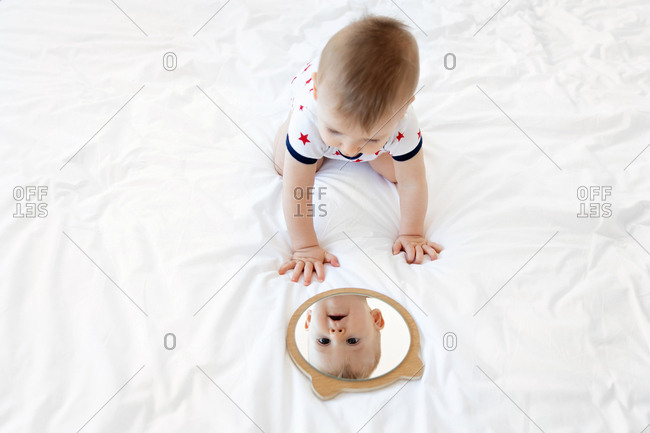 Baby looking in round mirror on bed