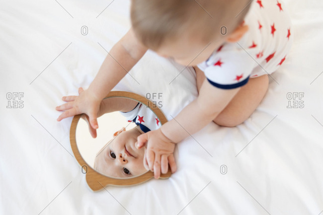 Baby looking in mirror on bed