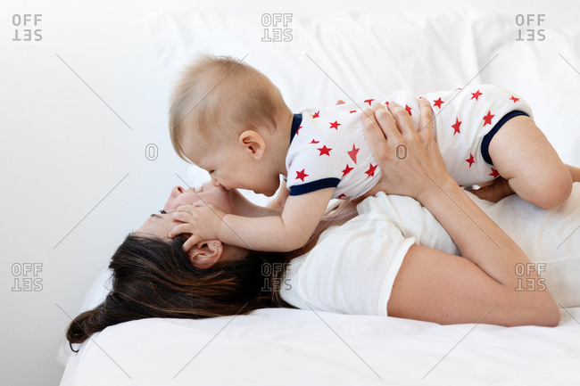 Mother holding baby while lying on bed