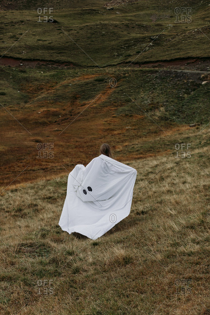 Person walking in field with ghost costume