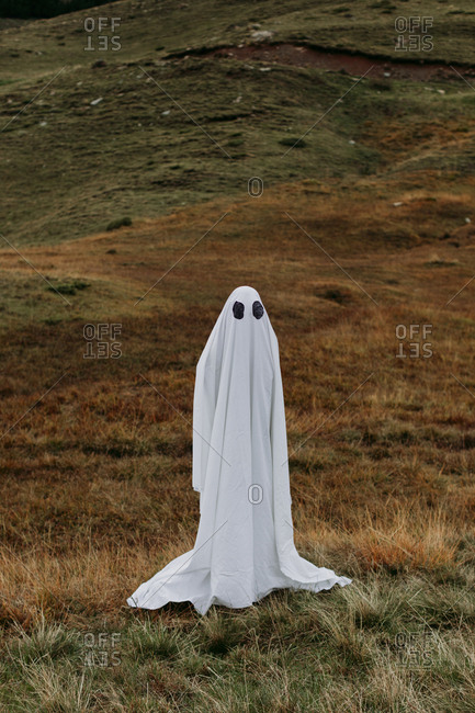 Person wearing white sheet as ghost costume
