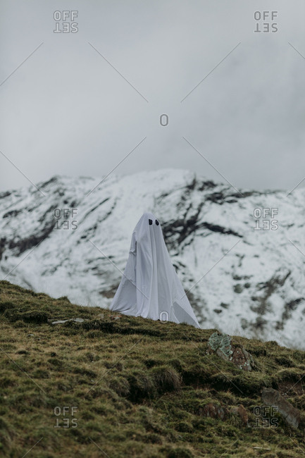 Person wearing ghost costume on mountainside