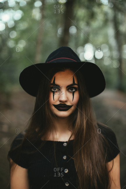 Girl wearing creepy makeup and hat for Halloween