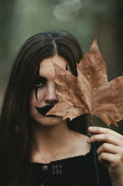 Girl wearing creepy makeup and leaf in front of her face