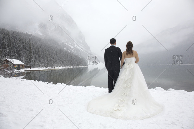 Chinese couple posing for wedding photographs in snow, Lake Louise, Banff National Park, Alberta, Canada