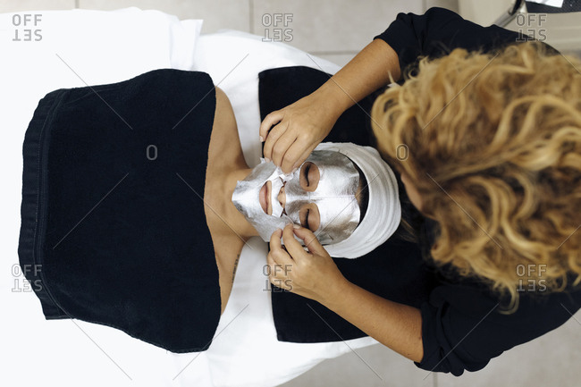 Woman having mask put on face in a spa