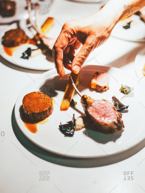 Chef holding lamb chops with his fingers