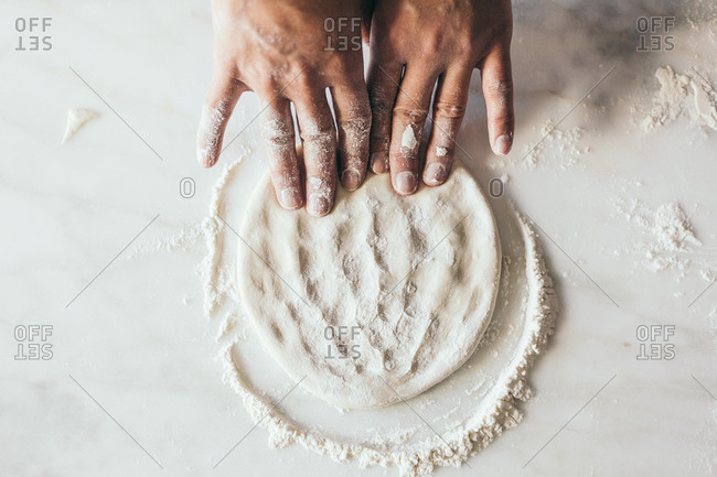 Man kneading dough with fingers