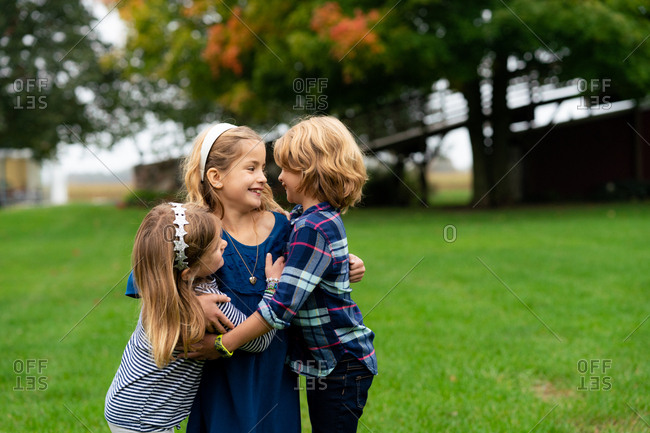 Three children embraced outdoors in fall