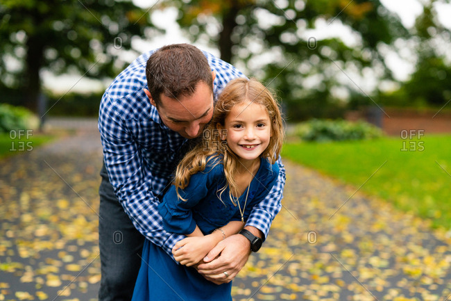 Father hugging daughter on path in fall