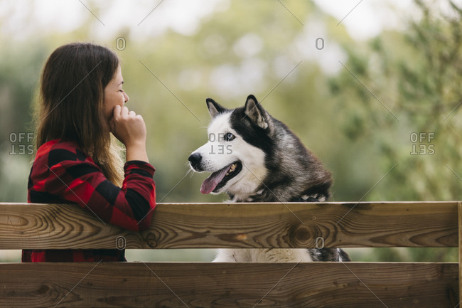 Young woman and her pet dog looking at each other