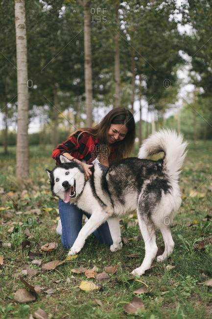 Young woman playing with her pet Husky dog