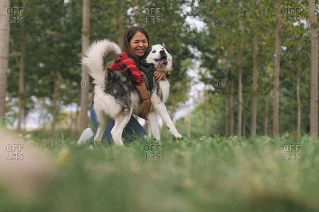 Young woman hugging her pet Husky dog