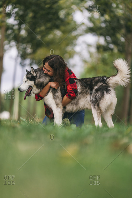 Young woman embracing her pet Husky dog