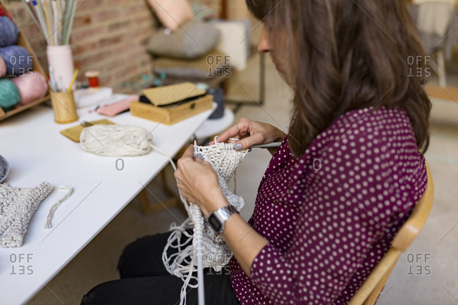 Woman sitting at table knitting with white yarn