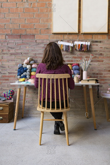 Back view of woman sitting at table with yarn and knitting supplies