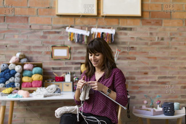 Smiling woman knitting with white yarn