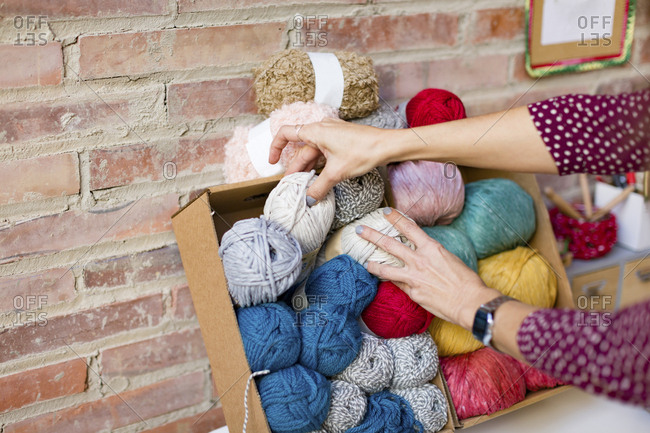 Woman selecting a skein of yarn from craft supplies