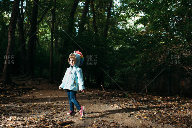 Little girl in a unicorn hoodie alone in the forest