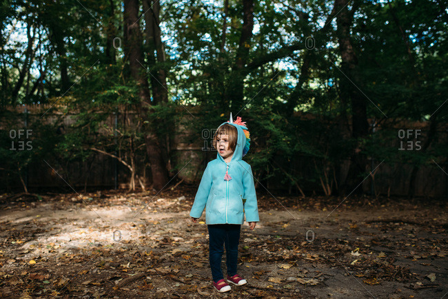 Little girl in a unicorn hoodie in the woods