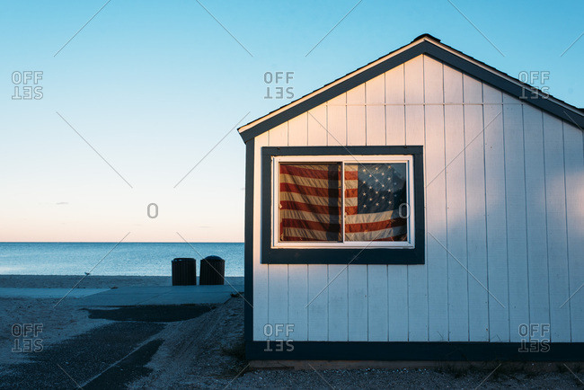 Building with an American flag in the window near the beach
