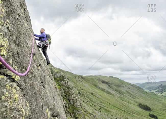 UK- Lake District- Longsleddale valley- Buckbarrow Crag- man climbing in rock wall