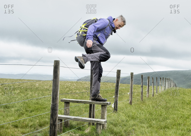 UK- Lake District- Longsleddale valley- mature man with backpack crossing pasture fence