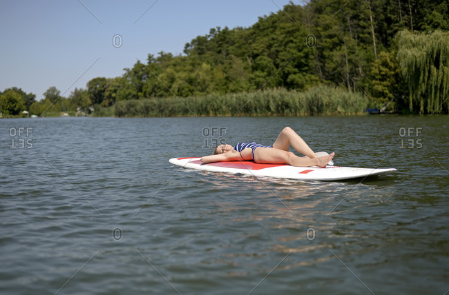 Germany- Brandenburg- woman relaxing on paddleboard on Zeuthener See