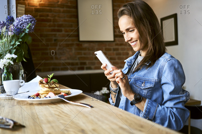 Smiling young woman with plate of pancakes using phone in cafe