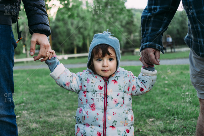 Portrait of fashionable little girl walking through a park on grandfather's and father's hands