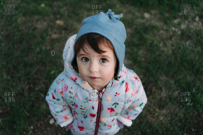 Portrait of fashionable little girl standing on a meadow in autumn