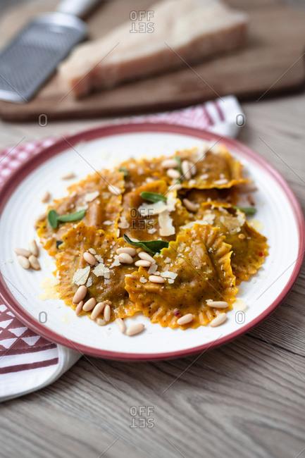 Plate of pumpkin ravioli with sage leaves- parmesan and pine nuts