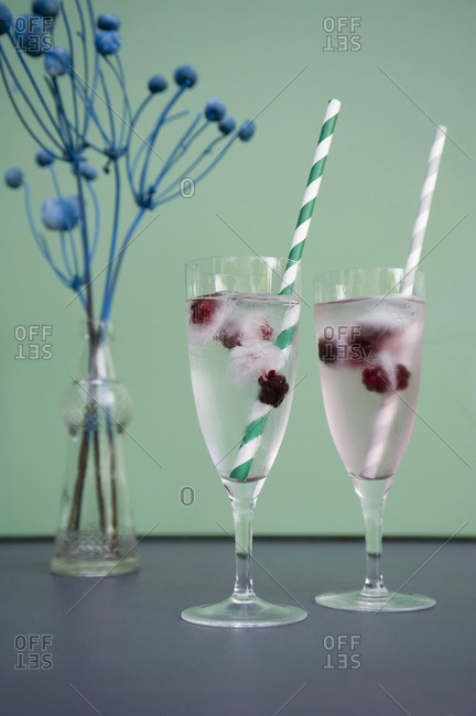 Ice cubes with blackberries in champagne glasses- dried flowers in vase