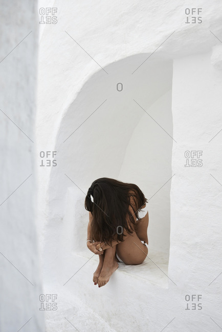 Young woman crouching in a wall niche